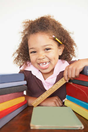 casualness: Mixed Race girl with stacks of books LANG_EVOIMAGES