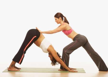 Yoga Trainer unterstützen schwangere Frau