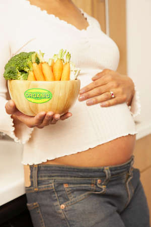 native american baby: Pregnant Mixed Race woman holding bowl of vegetables