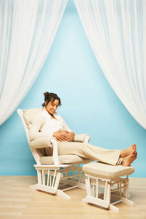milepost: Pregnant Mixed Race woman sitting in rocking chair