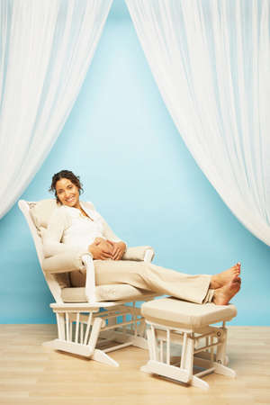 jewish home: Pregnant Mixed Race woman sitting in rocking chair