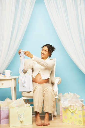 jewish home: Pregnant Mixed Race woman opening gifts