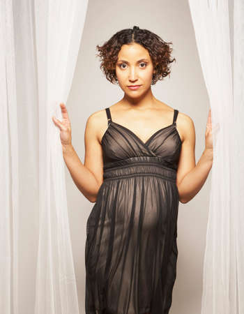milepost: Pregnant Mixed Race woman standing in curtains LANG_EVOIMAGES