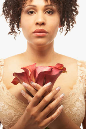 womanly: Mixed Race woman holding flowers LANG_EVOIMAGES