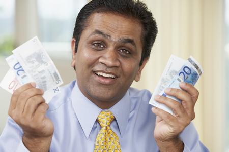 economizing: Middle Eastern man holding money