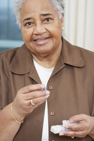 gusto: Senior African American woman holding medication