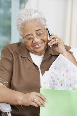 black baby girl: Senior African American woman talking on cell phone LANG_EVOIMAGES