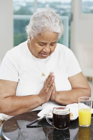 eagerness: Senior African American woman saying grace