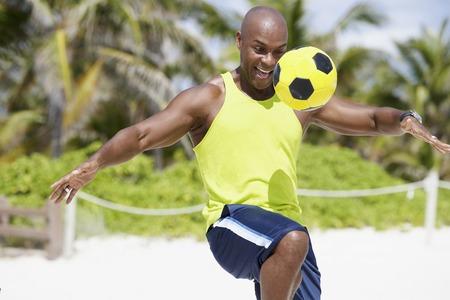de rodillas: Hombre afroamericano rebotando bal�n de f�tbol en la rodilla