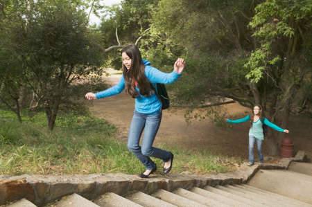teenaged girls: Hispanic teenaged girls walking up stone steps LANG_EVOIMAGES
