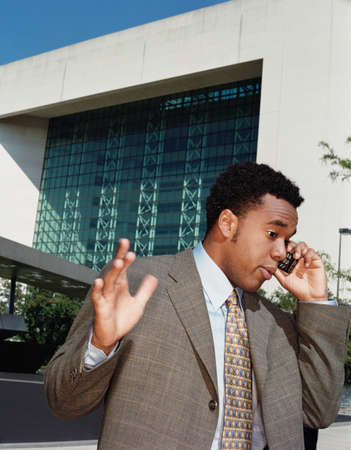businessman waiting call: African American businessman talking on cell phone