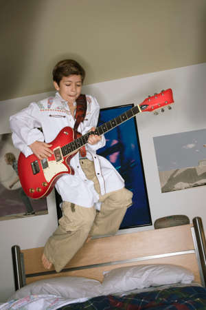 boy playing guitar: Boy playing guitar and jumping on bed LANG_EVOIMAGES