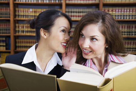 seriousness skill: Multi-ethnic women whispering in law library