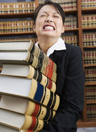 paralegal: Asian woman carrying stack of library reference books