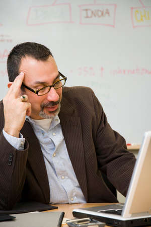 restfulness: Hispanic businessman looking at laptop LANG_EVOIMAGES