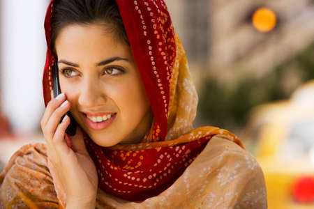 attired: Middle Eastern woman talking on cell phone