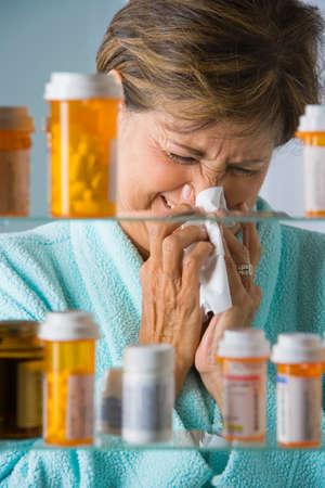 recuperating: Senior Hispanic woman blowing nose