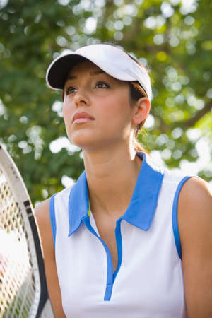 jeopardizing: Hispanic woman holding tennis racket