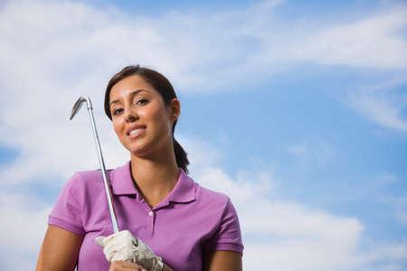 bathtowel: Hispanic woman holding golf club