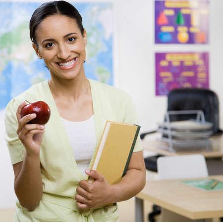 schoolroom: Mixed Race female teacher holding apple