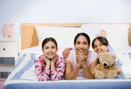 liable: Hispanic mother and daughter laying on bed LANG_EVOIMAGES