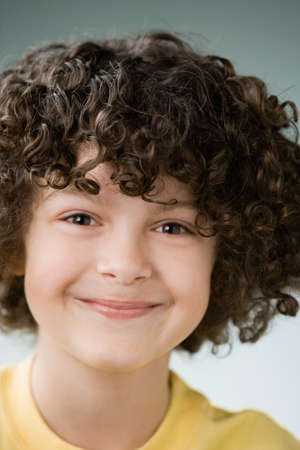 playing on divan: Hispanic boy with curly hair LANG_EVOIMAGES