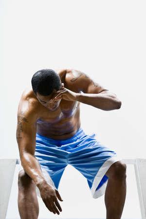 bathtowel: African American man rubbing sweat off forehead