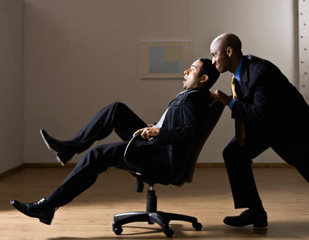 conferring: African American businessman pushing coworker in chair