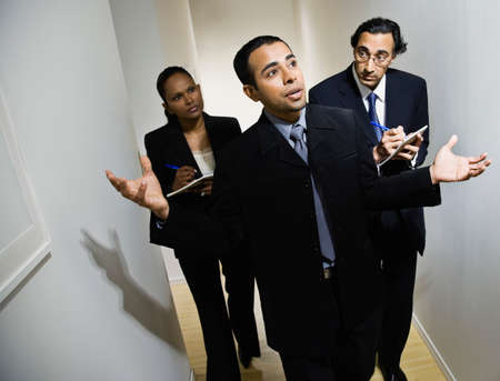 dictating: Multi-ethnic businesspeople walking in hallway