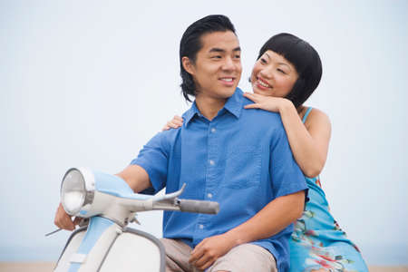 liveliness: Asian couple sitting on motor scooter