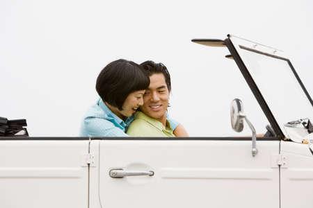 honeymooner: Asian couple hugging in convertible