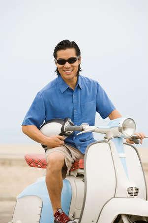 attired: Asian man sitting on motor scooter