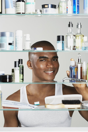 relishing: African man looking in medicine cabinet LANG_EVOIMAGES