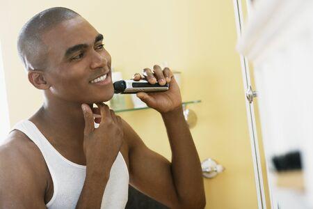electric razor: African man shaving with electric razor