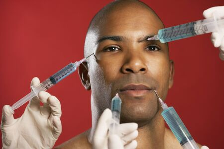 African American man receiving injections in face Stock Photo