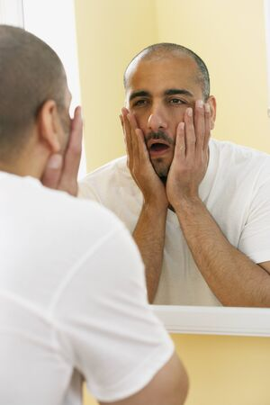 middle eastern: Middle Eastern man looking in mirror