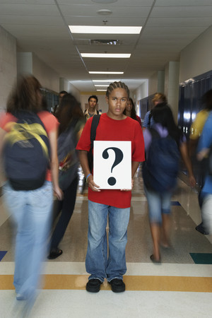 African American teenaged student holding question mark sign Фото со стока
