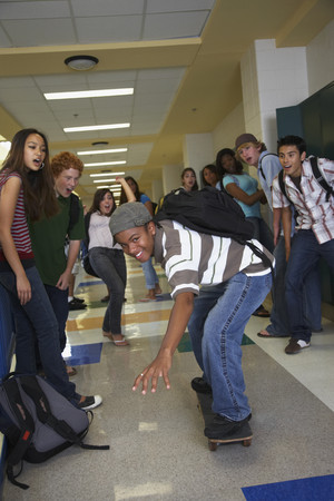 interrogating: African American teenaged boy riding skateboard in school hallway