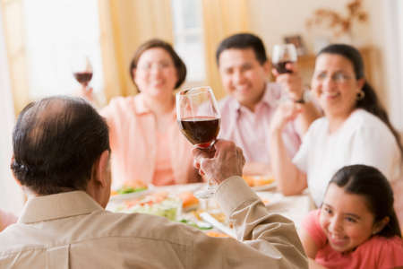 family  room: Hispanic family toasting at dinner table