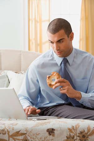 typist: Hispanic businessman looking at laptop LANG_EVOIMAGES