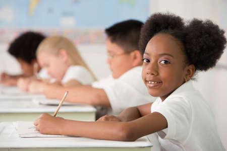 children learning: Multi-ethnic children writing at desks in classroom LANG_EVOIMAGES