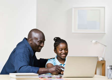 mischeif: African father and daughter looking at laptop