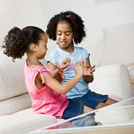 pacific islander ethnicity: Mixed Race sisters playing game LANG_EVOIMAGES