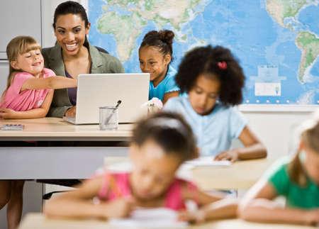 ni�os vistiendose: Profesora de la raza mezclada y estudiantes que buscan en la computadora port�til