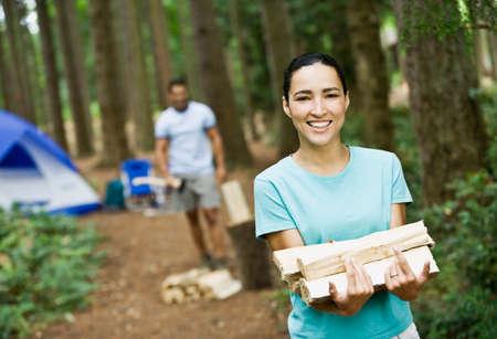 attired: Hispanic woman carrying chopped wood