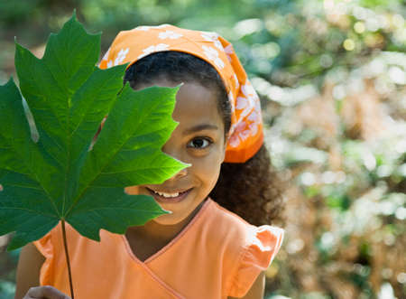 Mixed Race girl holding leaf in front of face Stock Photo