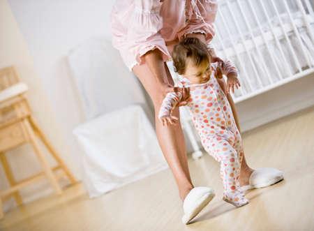 pacific islander ethnicity: Hispanic mother helping baby walk