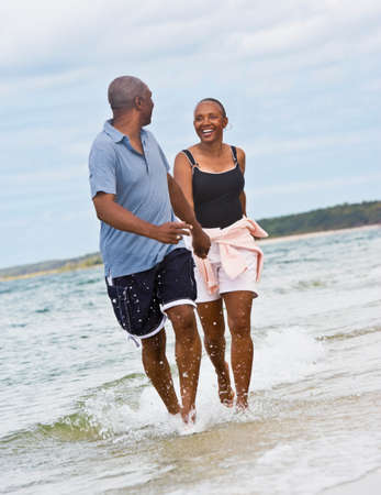 acknowledging: Senior African American couple running at beach LANG_EVOIMAGES