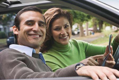 Hispanic Coupé hält Karte in Auto LANG_EVOIMAGES