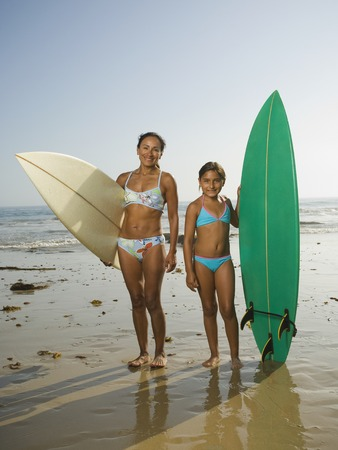 Hispanic mother and daughter holding surfboards